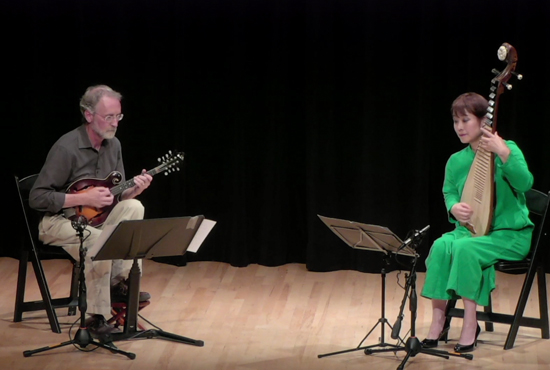 Two people on stage playing mandolins